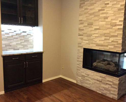 fireplace remodel, stone surround, dark cabinets, shaker cabinets, glass front cabinets, stone back splash, dry stack stone, add wet bar, granite countertop