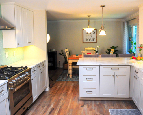 kitchen remodel, white cabinets, shaker cabinets, glass back splash, light green back splash, quartz counter top, stainless steel gas range, stainless steel hood, microwave cabinets, brushed nickel hardware, wall removal