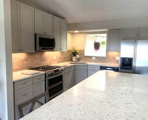 kitchen remodel, wall removal, light gray cabinets, stainless steel appliances, new kitchen island, undermount sink, accent cabinets, shaker cabinets, wood floors, dry stack stone, stone tile backsplash, quartz counter tops
