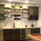 wet bar remodel, dry stack stone, stone back splash tile, dark cabinets, shaker cabinets, built in wine rack, stainless steel, wine fridge, dishwasher, custom shelving, rustic shelves, pipe shelves, under mount sink