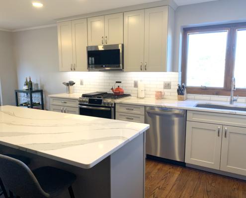 White cabinets, Stainless Steel Appliances, Breakfast Bar, Subway Tile Backsplash, Quartz Counter
